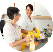caregiver and old woman cleaning dishes