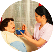 caregiver servcing foods to an old woman