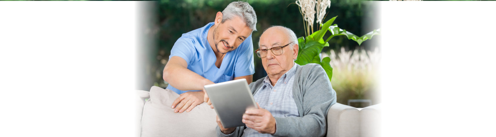 old man and caregiver using tablet