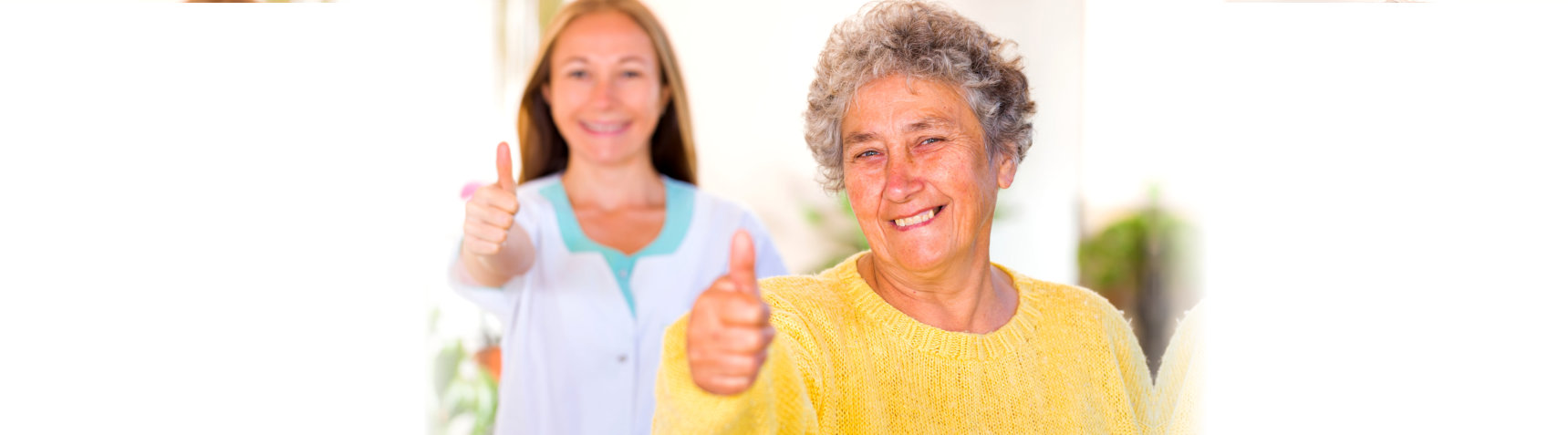 smiling caregiver and old woman doing thumbs up
